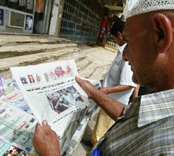 مواطن عراقي يطالع إحدى الصحف المحلية التي تبرز قضية المنتخب (صباح عرار ـ أ ف ب)