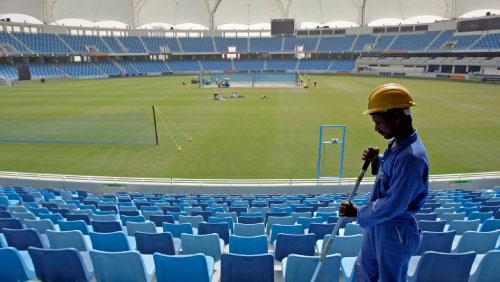 عامل ينظّف منصّة الحضور قبيل لعبة كريكيت في المدينة الرياضيّة في دبي (كامران جبريلي ــ أ ب)
