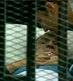مبارك خلف القضبان في المشاهد التي نقلها التلفزيون المصري قبل قطع الإرسال (رويترز)