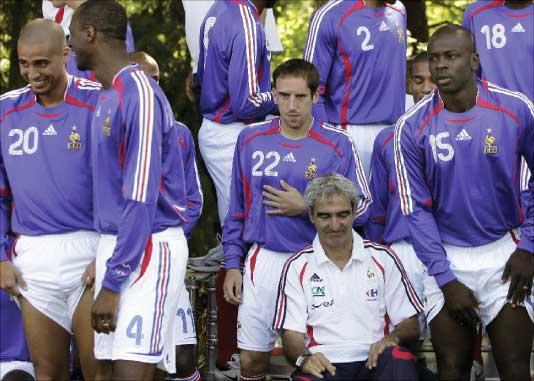 المدرب الفرنسي ريمون دومينيك (في الوسط) محاطاً بعدد من لاعبيه في مقر تدريب المنتخب في كليرفونتين (أ ب)