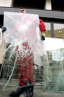 عامل يزيل الزجاج المتضرّر من المكان الذي سقط فيه القتيل (أ ب)