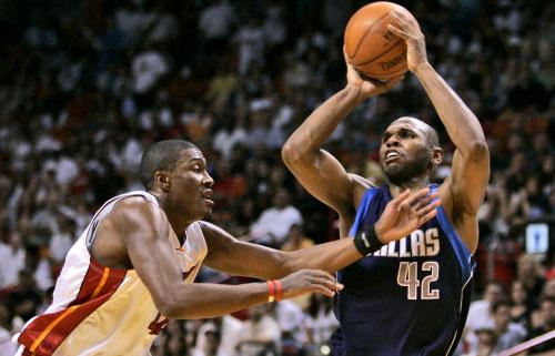 جيري ستاكهاوس من دالاس مافريكس مرسلاً الكرة الى السلة من فوق لاعب ميامي هيت جيمس بوزي (أ ب)