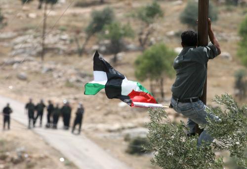 فلسطيني يرفع علم بلاده على عامود وأمامه جنود اسرائيليون في الضفّة الغربية أمس (عباس موماني - أ ف ب)