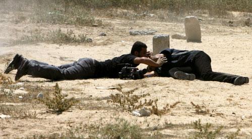 فلسطيني يساعد مصوراً من تلفزيون «الأقصى» بعد إصابته برصاص إسرائيلي أمس (محمد عبد - أ ف ب)