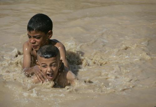 السباحة في مياه آسنة في بغداد (أرشيف - رويترز)