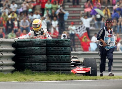 هاميلتون يخرج من سيارته الغارقة في الحصى خلال سباق شنغهاي (أوجين هوشيكو ـ أ ب)