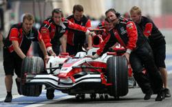مهندسو «سوبر اغوري» يدخلون سيارة ساتو إلى الحظيرة خلال سباق البحرين (مروان نعماني ـ أ ف ب)