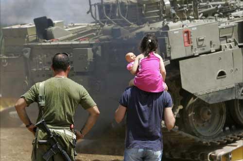 إسرائيليون يراقبون شحن ناقلة جند في مستوطنة كريات شمونة شمال الأراضي آ onblur