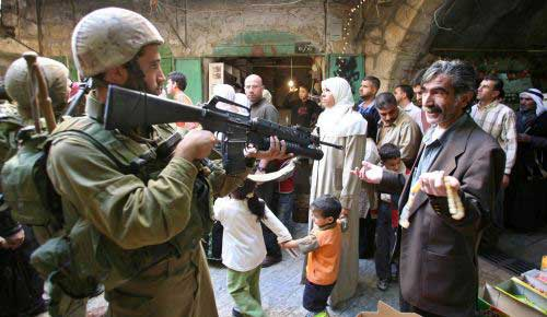 جندي إسرائيلي يصوّب بندقيته على مواطن فلسطيني في الخليل أمس (رويترز)