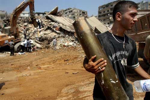 شاب يحمل بقايا قذيفة إسرائيلية في الضاحية (أ ف ب)
