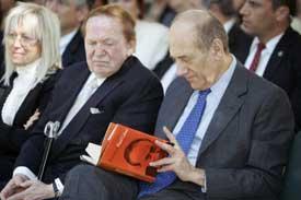 اولمرت يقرأ كتاباً خلال احتفال لتكريم المانحين أقيم عند نصب ياد فاشيم للهولوكوست في القدس المحتلة (أ ب)