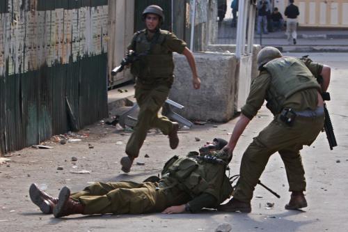 جندي إسرائيلي يسحب آخر أصيب بالحجارة في الخليل في الضفة الغربية أمس (أ ب)