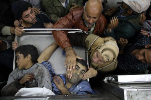 قريبة لأحد الشهداء تتعرف إلى جثمانه في مشرحة مستشفى بيت حانون (أ ف ب)