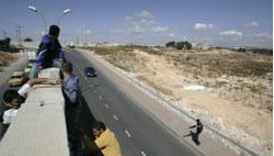 فلسطينيّون يتسلّقون الجدار الفاصل في بلدة الرام في الضفّة الغربيّة (أرشيف-أ ب)