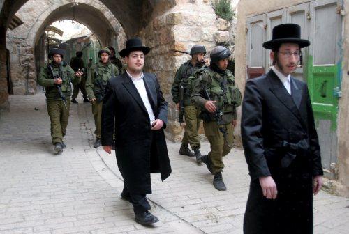 جنود إسرائيليّون يرافقون مستوطنين في الخليل في الضفّة الغربيّة السبت الماضي (إي بي أي)