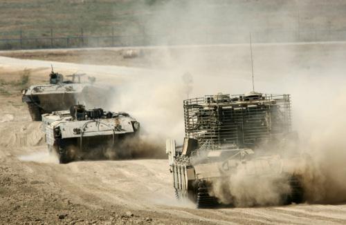 دبابات إسرائيلية خلال عودتها إلى جنوب إسرائيل بعد عملية في قطاع غزة أمس (أرييل شاليط - أب)