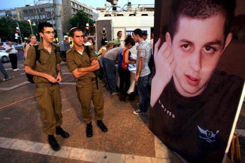 جنديّان إسرائيليّان أمام ملصق لصورة شاليط في تل أبيب في آب الماضي (بافل ولبرغ ـــ إي بي أي)