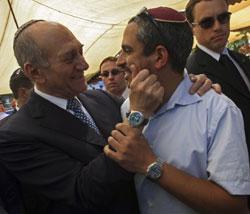 أولمرت يحيّي مناصراً له في القدس المحتلّة أمس (دايفيد سيلفرمان ـ أ ف ب)