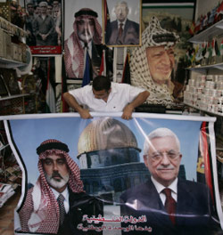 تاجر فلسطيني يبيع لافتة عليها صورتا عبّاس وهنيّة في غزّة أول من أمس (خليل حمرا ـ أ ب)