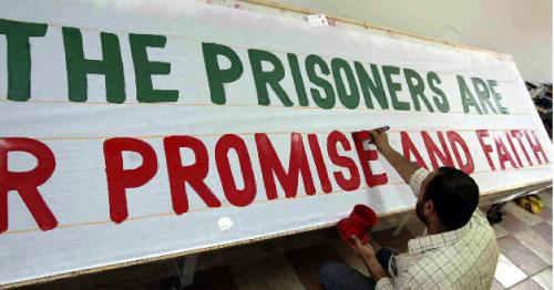 مناصر لحزب الله يضع لافتة تحضيراً لاستقبال الأسرى المحرّرين في النبطيّة (محمود الزيات ـــ أ ف ب)