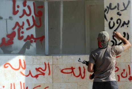 مقاتل من «شورى طالبان» يكتب شعارات اسلامية قرب معبر باب الهوى (بولنت كوليك - أ ف ب)