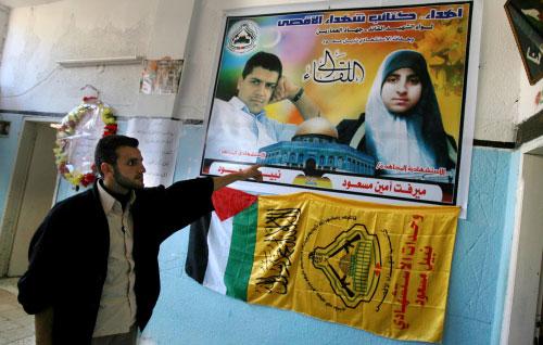 شقيق الاستشهادية ميرفت مسعود يقف أمام صورتها في منزل العائلة في قطاع غزة أمس (أ ف ب)