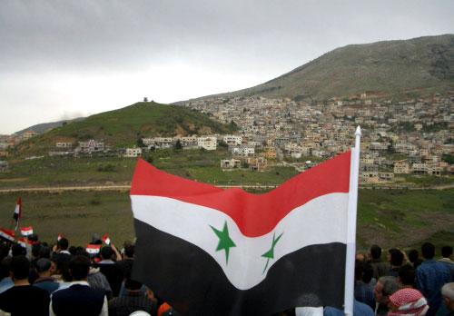 سوريون يرفعون علم بلادهم قبالة قرية مجدل شمس المحتلة في الجولان في 17 نيسان (أ ف ب)