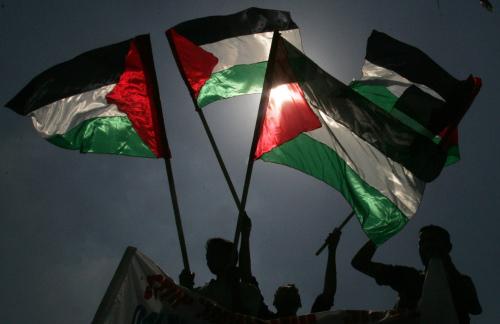 عمال يلوّحون بالأعلام الفلسطينية خلال تظاهرة للمطالبة بحقوقهم في غزة أمس (خليل حمرا ــ أ ب)