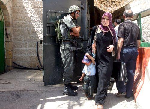 جندي إسرائيلي يدقق في هويات المارة في الخليل أمس (عبد الحفيظ هشلمون - إي بي أي)