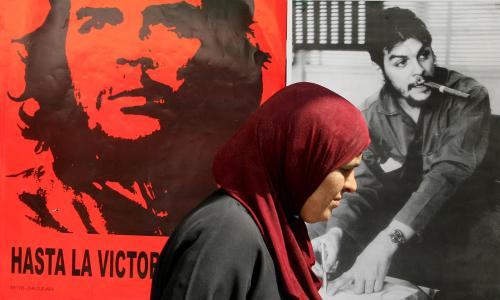 فلسطينيّة أمام صورتين لإرنستو غيفارا في معرض بمناسبة ذكرى استشهاده في جنين أمس (سيف دحلاح ــ أ ف ب)