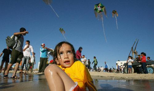أطفال فلسطينيّون يلهون على شاطئ غزّة أول من أمس (محمود حمس ـــ أ ف ب)