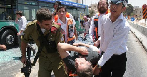 مسعفون إسرائيليّون ينقلون أحد جرحى العمليّة أمس (بريان هندلر ـــ أ ف ب)
