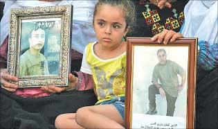 طفلة فلسطينية تحمل صورتي سجينين  (أ ف ب)
