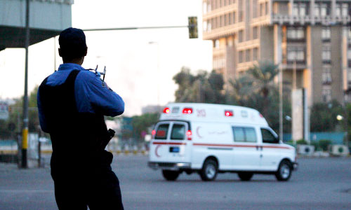 شرطي وسيارة إسعاف في موقع التفجير في وسط بغداد أمس (أ ب)