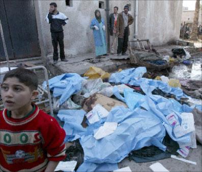 فتى عراقي قرب جثث ضاحايا انفجارات بغداد أمس (إي بي أي)