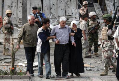 عراقيّون عند موقع تفجير في منطقة الكرّادة في بغداد أمس (خالد محمّد - أ ب)
