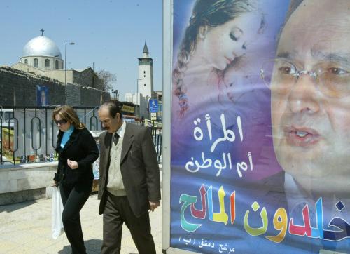 سوريان يمرّان قرب ملصق لأحد المرشّحين للانتخابات التشريعيّة في دمشق أمس (لؤي بشارة - أ ف ب)