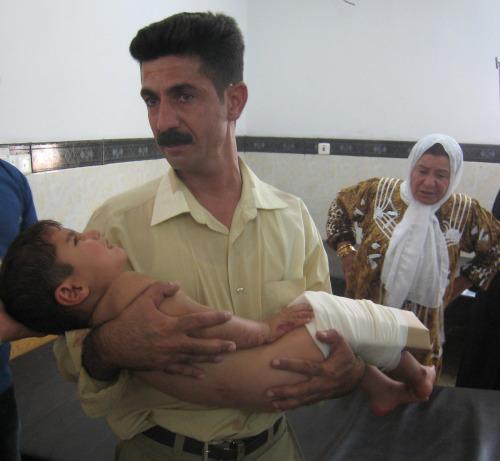 عراقي يحمل طفلاً مصاباً في كركوك أمس (عماد ماتي - أ ب)