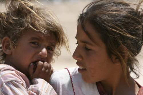 عراقية تحمل شقيقتها في مخيم للاجئين في حي الشعب في بغداد أمس (ثائر السوداني - رويترز)