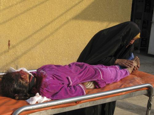 عراقيّة تمسك قدم ابنتها الجريحة في بعقوبة أمس (أ ب)