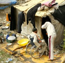 مقعَد عراقي نازح يدخل إلى خيمته في بغداد في آذار الماضي (علي يوسف ـ أ ف ب)