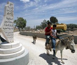 فلسطينيّان قرب مدخل قرية شمالي الضفّة حيث قرّرت سلطات الاحتلال هدم منازل (جاك غويز ـــ أ ف ب)