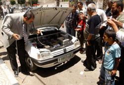 فلسطيني بالقرب من سيّارة كهربائية اخترعها في غزّة الأسبوع الماضي (محمد سالم ــ رويترز)