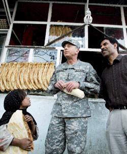 بترايوس «يختلط» مع السكان المحليين في أحد الأفران (أحمد مسعود ـ أ ب)