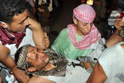 محتجون يسعفون احد الجرحى في تعز أول من أمس (أ ف ب)