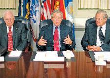 الرئيس الأميركي جورج بــوش يتوسط وزير الدفاع دونــالد رامسفيلد ونائبه ديك تشــيني خــلال حــديث