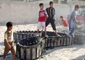 أطفال عراقيون يلهون على بقايا دبابة بريطانية أعطبها مسلحون في البصرة (أي بي أ)