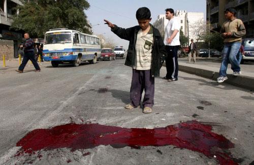 فتى عراقي ينظر إلى بقعة دماء خلّفها انفجار في وسط بغداد أمس (أ ب)