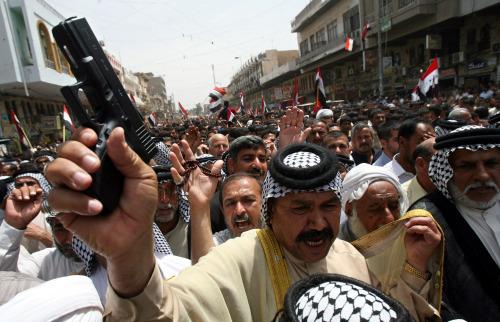 مناصر للتيّار الصدري يرفع مسدّسه خلال التظاهرة ضدّ الاحتلال في الكاظميّة أمس (هادي مزبان - أ ب)