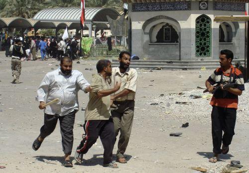 مقاتلون يحتجزون أحد المواطنين في كربلاء أمس (رويترز)